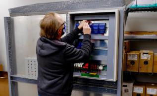Modern Niagara employee working on electric panel