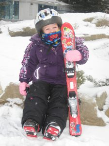 Young child in snow gear and skiing equipment holds onto a pair of skis.