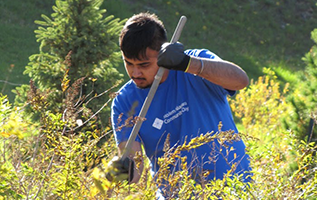 "A Modern Niagara employee, with a blue t shirt that reads ""Community Day,"" takes part in tree-planting."
