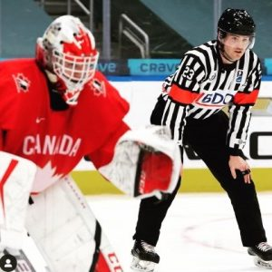 Tyson Stewart in full referee gear, standing behind the Canadian goalie at the 2021 World Juniors Hockey Tournament.