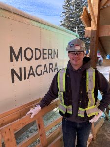 Tyson Stewart in safety gear, standing next to a branded Modern Niagara truck on a project site.